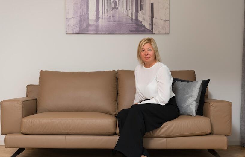 Симона Хардалова, брокер на недвижими имоти в агенция СИТИ ВИЛИДЖ, представяща всекидневна с бежов, кожен диван